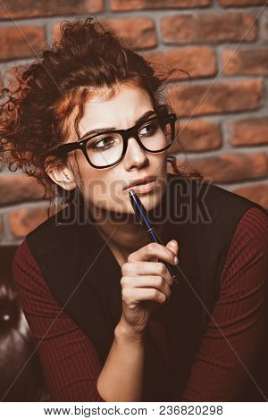 Portrait of a thoughtful business woman wearing glasses and formal clothes. Contemporary business.