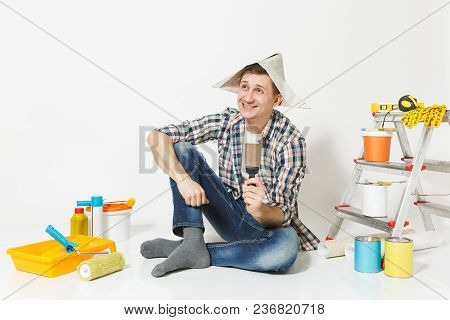 Happy Smiling Young Man In Newspaper Hat With Putty Knife Instruments For Renovation Apartment Room