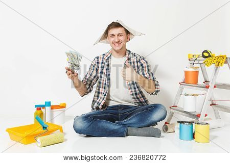 Happy Man In Newspaper Hat Holds Bundle Of Dollars, Cash Money. Instruments For Renovation Apartment