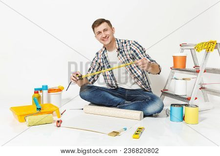 Young Man Sitting On Floor With Roll Of Wallpaper, Measure Tape, Pencil, Instruments For Renovation