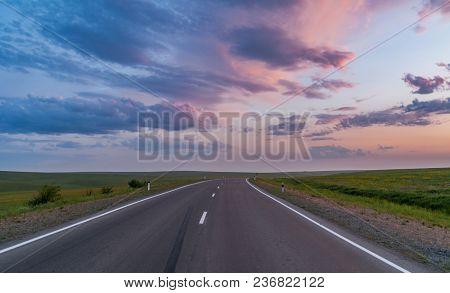 Empty Asphalt Road Through The Beautiful Field On Sunset