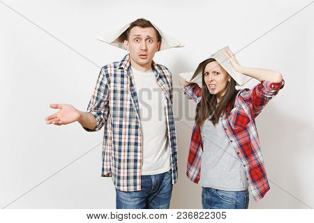 Young Dissatisfied Woman, Man In Casual Clothes And Newspaper Hats Spreading Hands. Couple Isolated