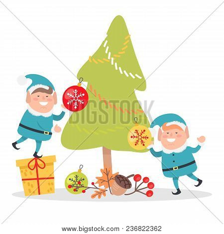Two Elves In Blue Santa Suits Decorate Christmas Tree Isolated On White Background. Little Elf Stand
