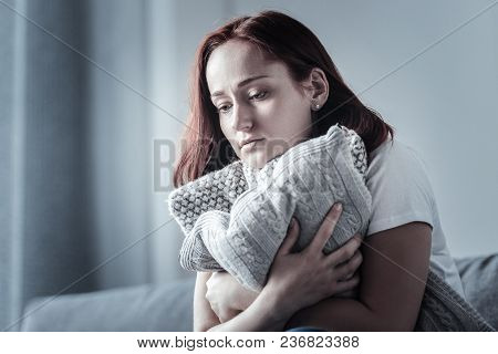 Little Warmer. Mournful Dolorous Bleak Woman Sitting With Pillow While Staring Down And Recalling Da