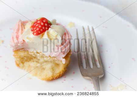 Pink Strawberry Cupcake On White Plate With Star Sprinkles, Half Eaten