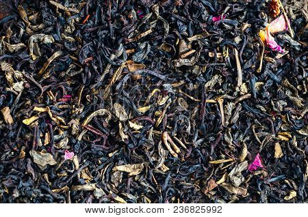 Black Tea As Background With Dry Rose Petals