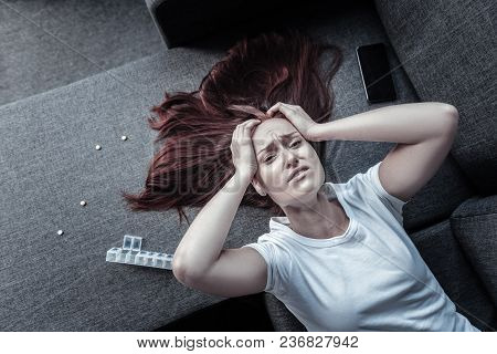 Mental Disorder. Top View Of Nervous Unsettled Unhappy Woman Touching Head While Posing On Sofa And