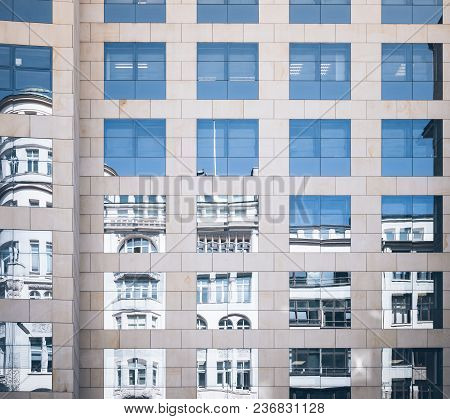 Historic Building Mirrored In Glass Facade Of Modern Office Building Old And New Contrasting Concept