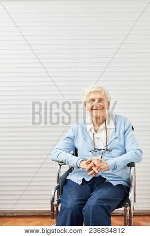 Old frail senior citizen sits smiling in wheelchair in retirement home