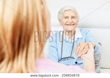 Nurse or nurse on home visit holding a senior's hand