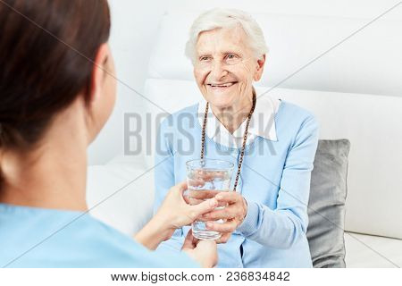 Female nursing assistant gives senior citizen a glass of water or medicine