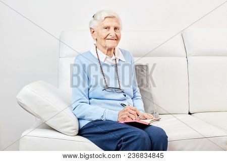 Happy old woman is sitting on the sofa at home or in a retirement home