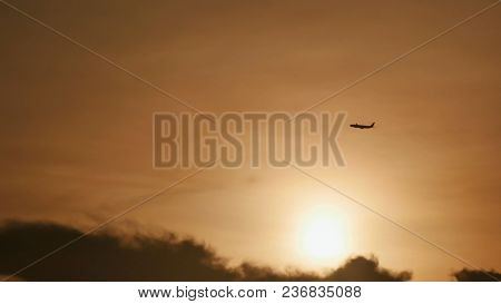 Take Off The Plane In The Distance Against The Background Of Sunrise Or Sunset. Silhouette Of An Air