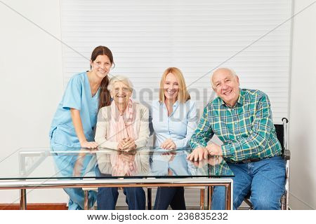 Caregiver and happy family with parents and daughter in a retirement home