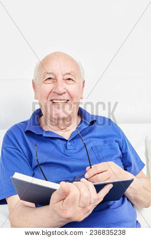 Happy senior as a pensioner reads a book at leisure in retirement home