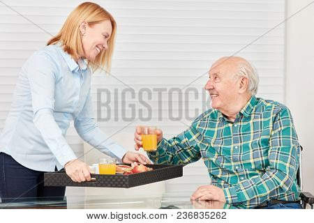 Young woman serves senior breakfast with juice on a tray at home