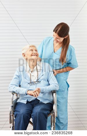 Old elderly woman in wheelchair being cared for by young caring wife at home