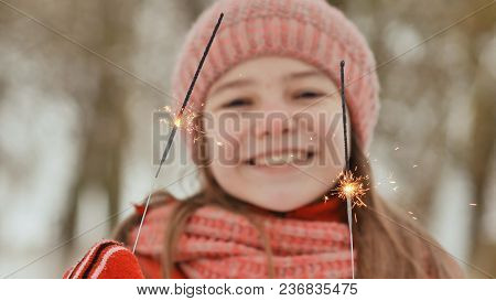 A Happy Young Schoolgirl With Sparkling Sparks Of Bengal Lights Among The Winter Forest. On The Eve