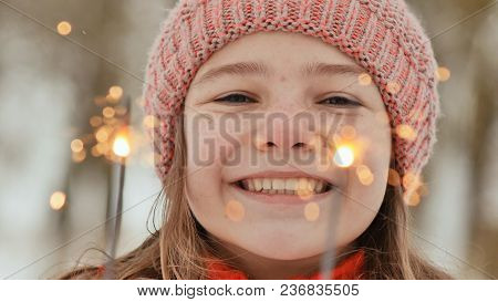 A Happy Young Schoolgirl With Sparkling Sparks Of Bengal Lights Among The Winter Forest. Face Close-
