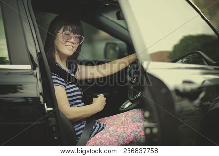 Younger Woman Sitting On Driver Seat Of Suv Car And Fasten Seat Belt