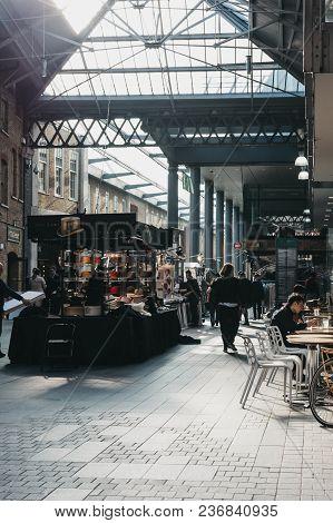 London, Uk - April 14, 2018: People Walking Past Market Stalls In Old Spitalfields Market, One Of Th