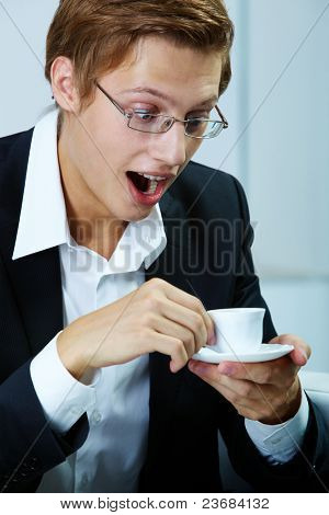 Portrait of astonished businessman looking into cup
