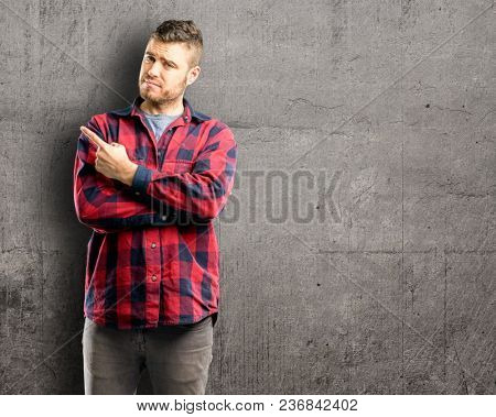 Young handsome man pointing away side with finger