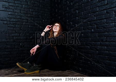 Studio Shoot Of Girl In Black With Dreads, At Glasses And Hat On Brick Background.