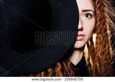 Studio Shoot Of Girl In Black With Dreads And Hat On Brick Background.