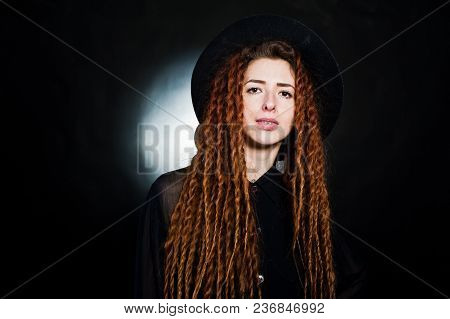 Studio Shoot Of Girl In Black With Dreads And Hat At Black Background.