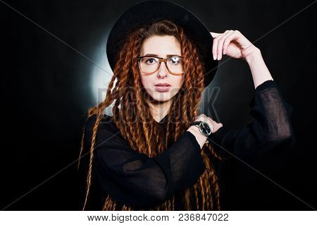 Studio Shoot Of Girl In Black With Dreads, Hat And Glasses At Black Background.