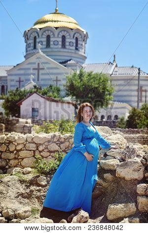 Pregnant Redhead Woman Standing Near The Church
