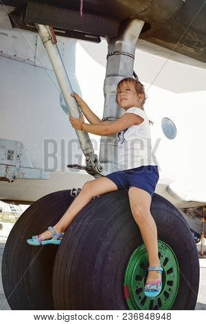 Little Girl On The Plane Exhibition Sitting On The Wheel Of Plane