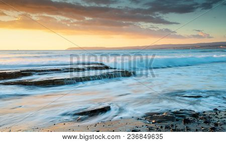 Rocky Seashore During Sunset With Wavy Ocean And Waves Crashing On The Rocks At Akrotiri Coast Area