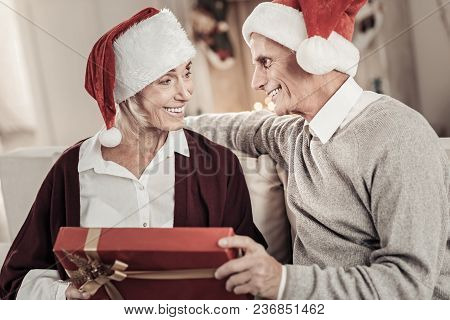Love You. Handsome Man Sitting In Semi Position And Embracing His Wife While Presenting Gift