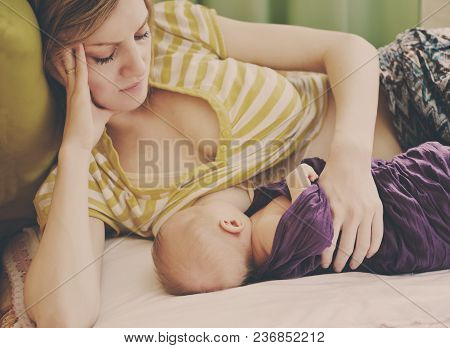 Young Mother Is Breastfeeding Her Baby Infant
