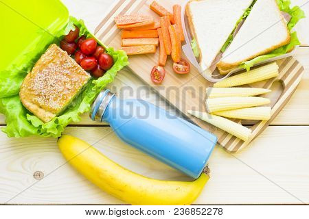 Healthy Lunch Concept. Lunch Box Food Assortment: Sandwich, Fruit, Vegetable, Blue Bottle, Light Woo