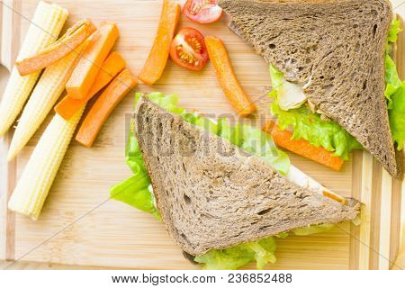 Healthy Lunch Concept. Lunch Box Food Assortment: Rye And Wheat Bread Sandwich And Vegetables On Woo
