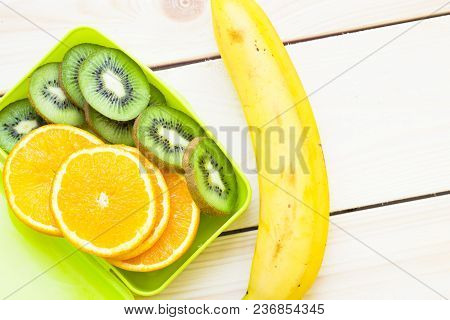 Healthy Lunch Concept. A Green Lunch Box With Sliced Orange And Kiwi And Banana, Light Wooden Backgr