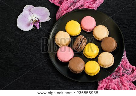 Different Macaroon On Black Plate And Orchid On Slate Background. Delicious And Sweet Almond Cookies