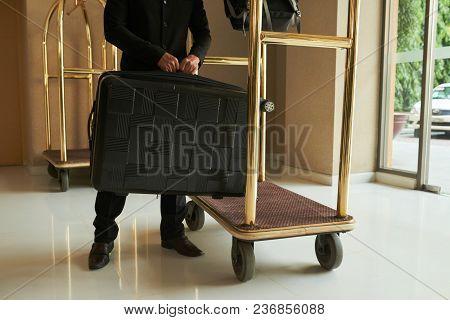 Cropped Iamge Of Hotel Servant Putting Luggage On Cart
