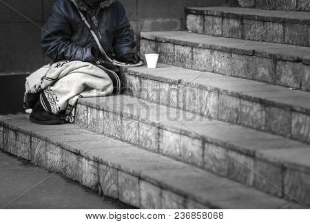 Homeless poor woman begging for money outdoors