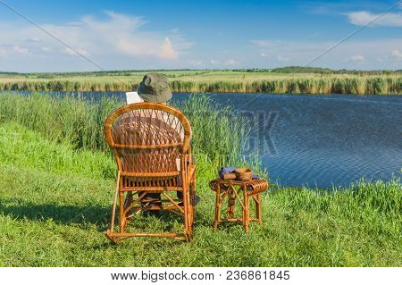 Senior Man Reading Book While Sitting In The Wicker Rocking-chair On A Riverside At Summer Season