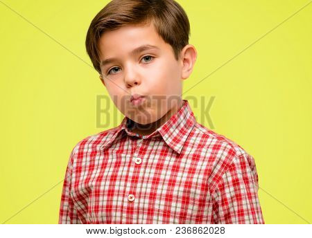 Handsome toddler child with green eyes puffing out cheeks, having fun making funny face over yellow background