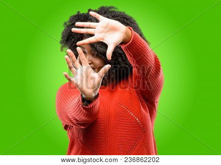 Beautiful african woman confident and happy showing hands to camera, composing and framing gesture