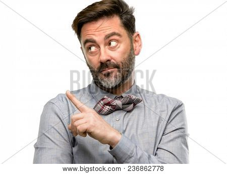 Middle age man, with beard and bow tie pointing away side with finger isolated over white background