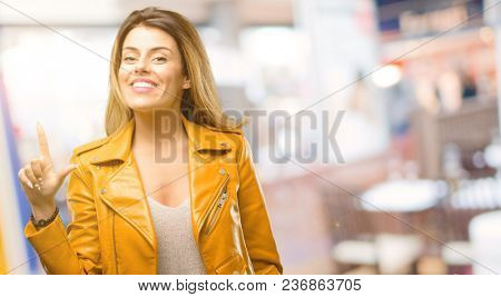Beautiful young woman pointing away side with finger at restaurant
