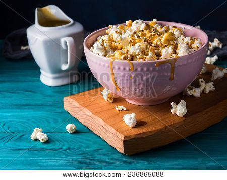Popcorn With Salted Caramel In Pink Bowl On Wooden Board On Dark Background