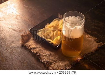 Glass Of Beer And Potato Chips On A Wooden Table