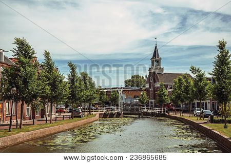 Tree-lined Canal With Bascule Bridge, Church And Brick Houses In Street On The Banks On Sunny Day In